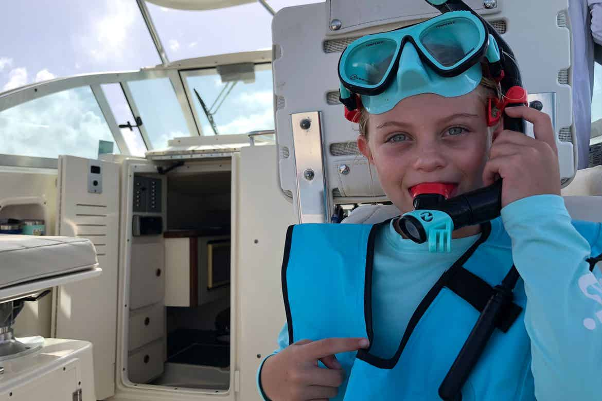 Featured Contributor, Chris Johnston's daughter, Kyndall, wears her Wacool snorkel vest and gear while sitting on a boat in the ocean.