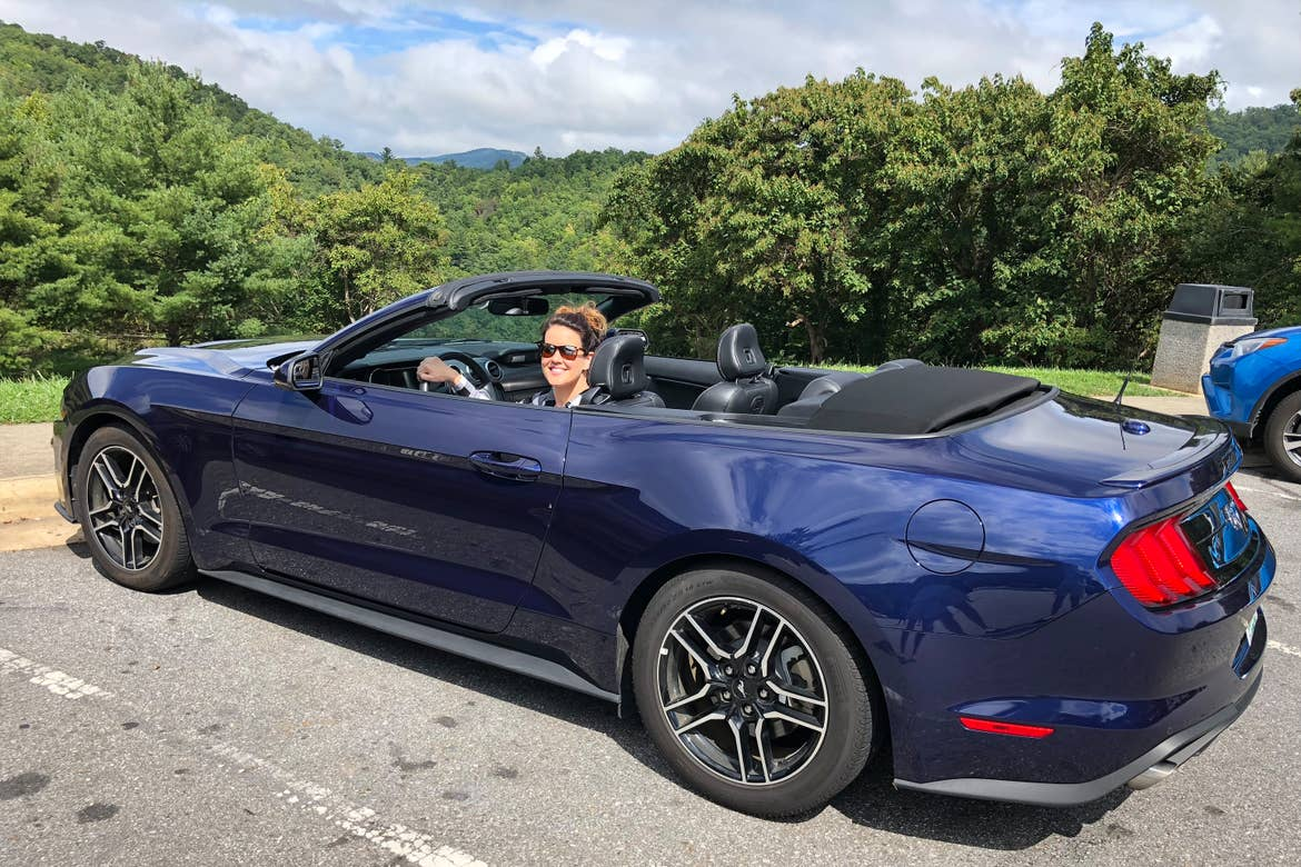 Jenn C. Harmon sits in the driver's seat of a dark blue Mustang convertible surrounded by lush foliage near the Great Smoky Mountains.