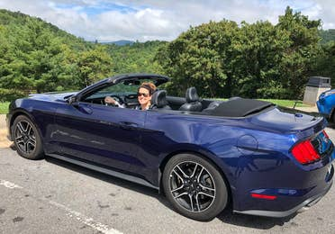 Jenn C. Harmon sits in the drivers seat of a dark blue Mustang convertible surrounded by lush foliage in LA.