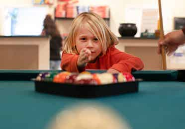A young child at a pool table