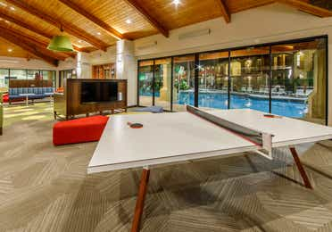 Table tennis and television in a game room with doors looking out to a pool