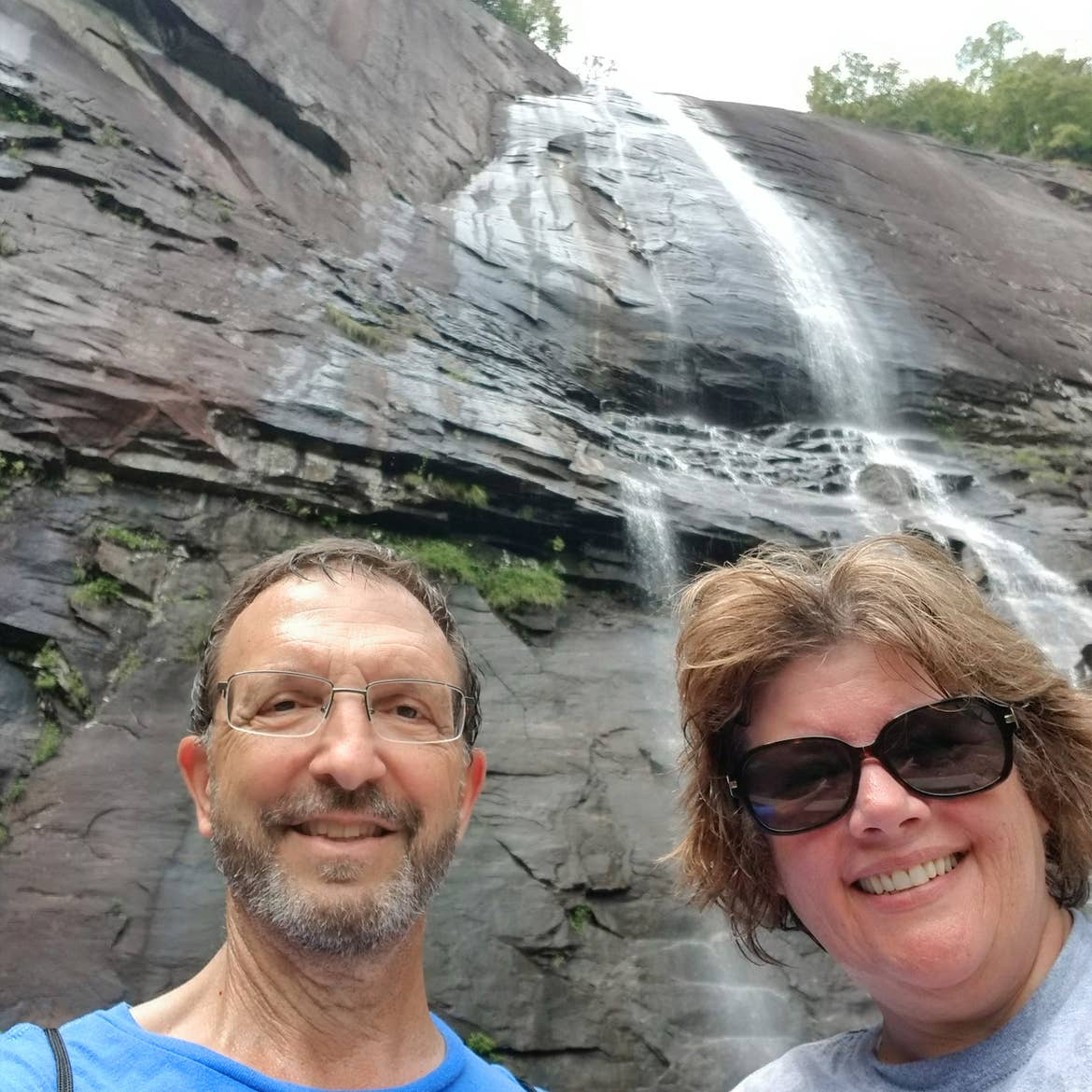 A caucasian male wearing a blue t-shirt (left) and a caucasian female wearing a light colored t-shirt (right) stand under the Hickory Nut Falls in Chimney Rock State Park, North Carolina.