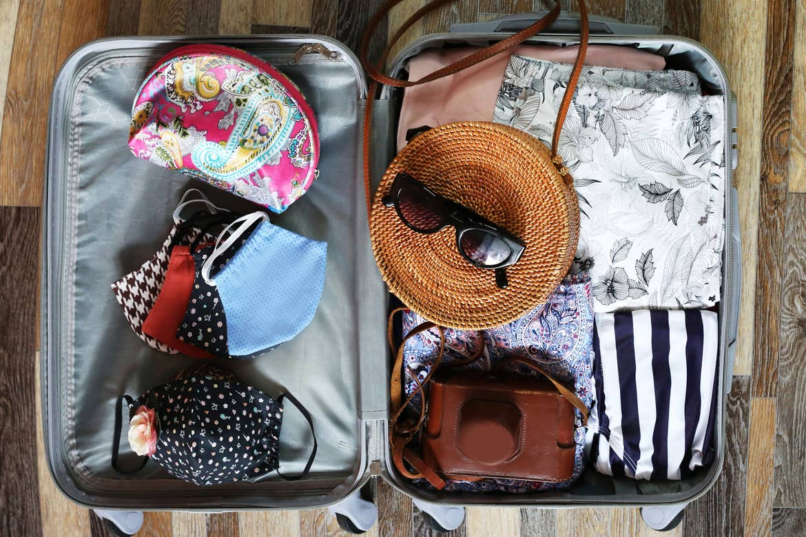 An open suitcase containing women's clothing, masks, bags, and accessories.