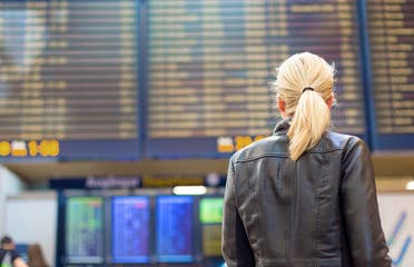 A blonde woman faces an airport Departure board in the terminal while wearing a black leather jacket.