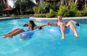 A young boy (right) and a young girl (left) sit in inner tubes while floating down a lazy river.