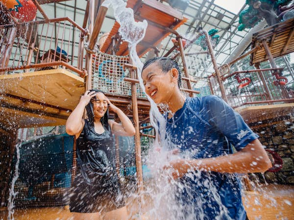 Two kids standing under water bucket at Waterpark at the Villages in Flint, Texas.