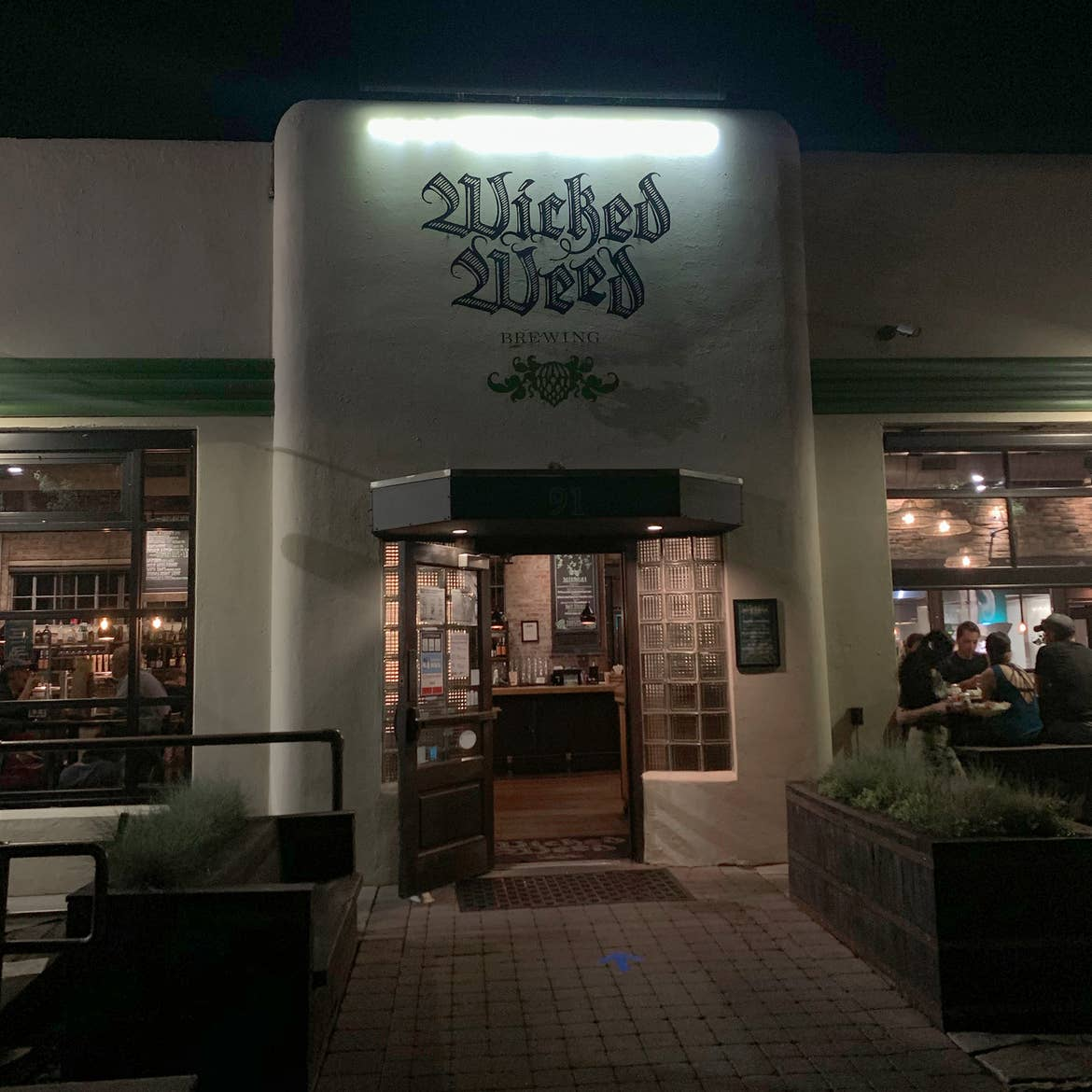 Brewery exterior with stucco white walls and painted sign that reads, 'Wicked Weed' in green.