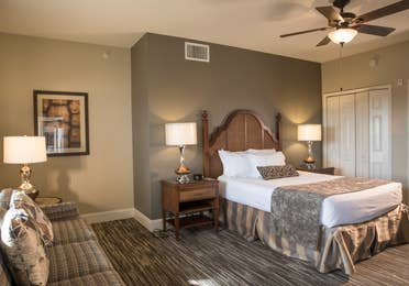 Bedroom with ceiling fan and seating area in a four bedroom Signature villa in River Island at Orange Lake Resort near Orlando, Florida