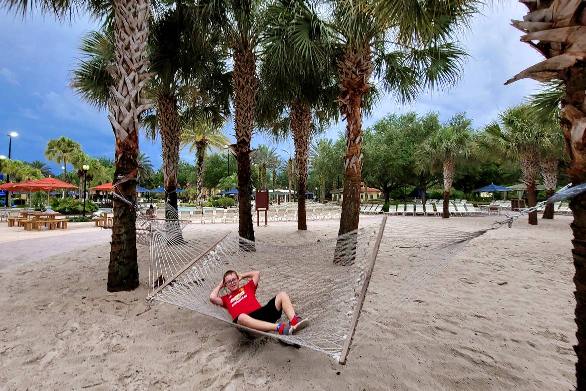 A young boy sits on a hammock under palm trees.