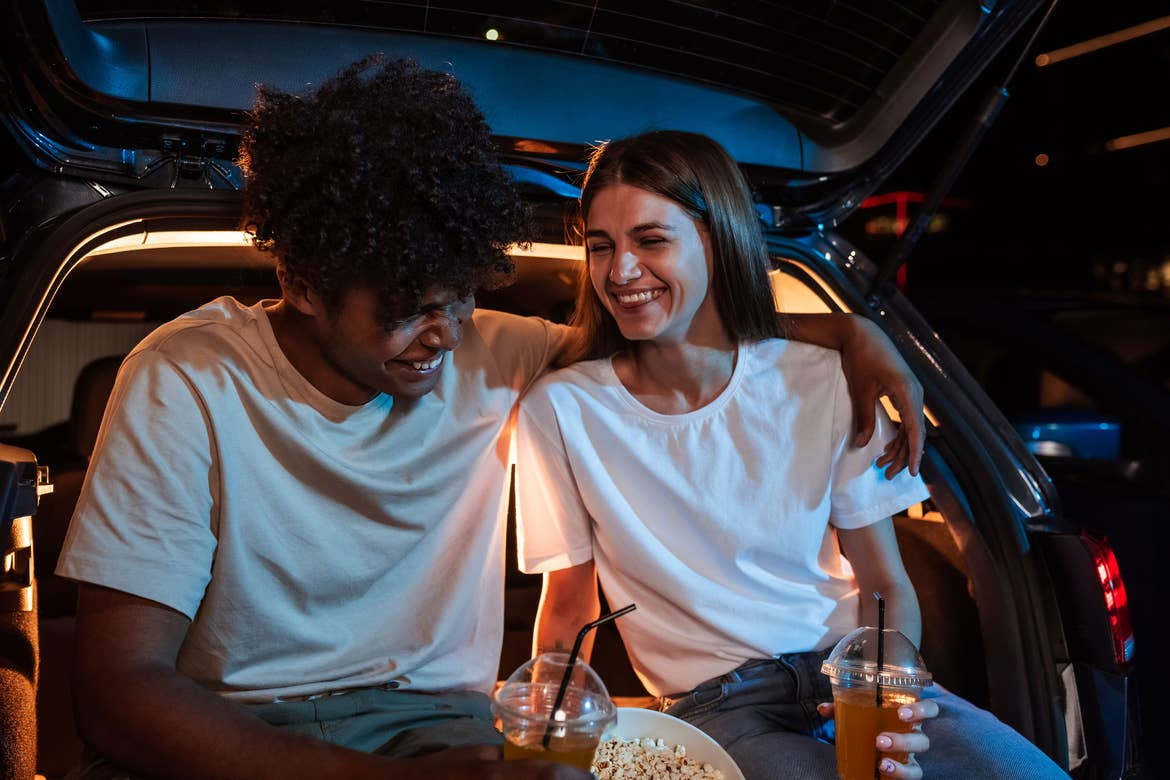 Couple at drive-in sitting in hatchback with food and beverages.
