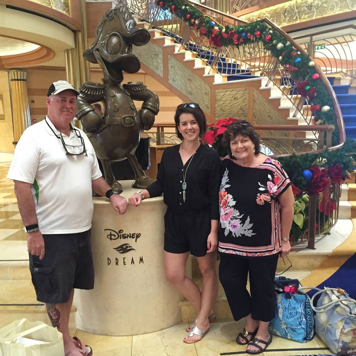 A man wearing a white and black cap, white polo and black shorts stands to the left of two women - both wearing black blouses and pants - and a bronze statue of Donald Duck on a pedestal that reads, 'Disney Dream.'