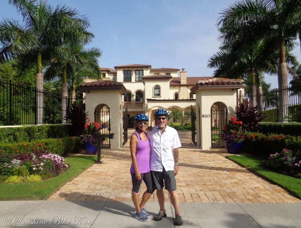 Denise and CJ with helmets on posing in front of a mansion on Marco Island
