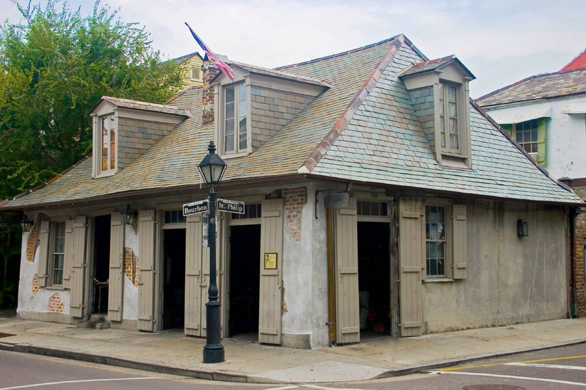 The exterior of LaFitte's Blacksmith Shop Bar is constructed of various brick and mortar with doorways that open like wooden shutters.
