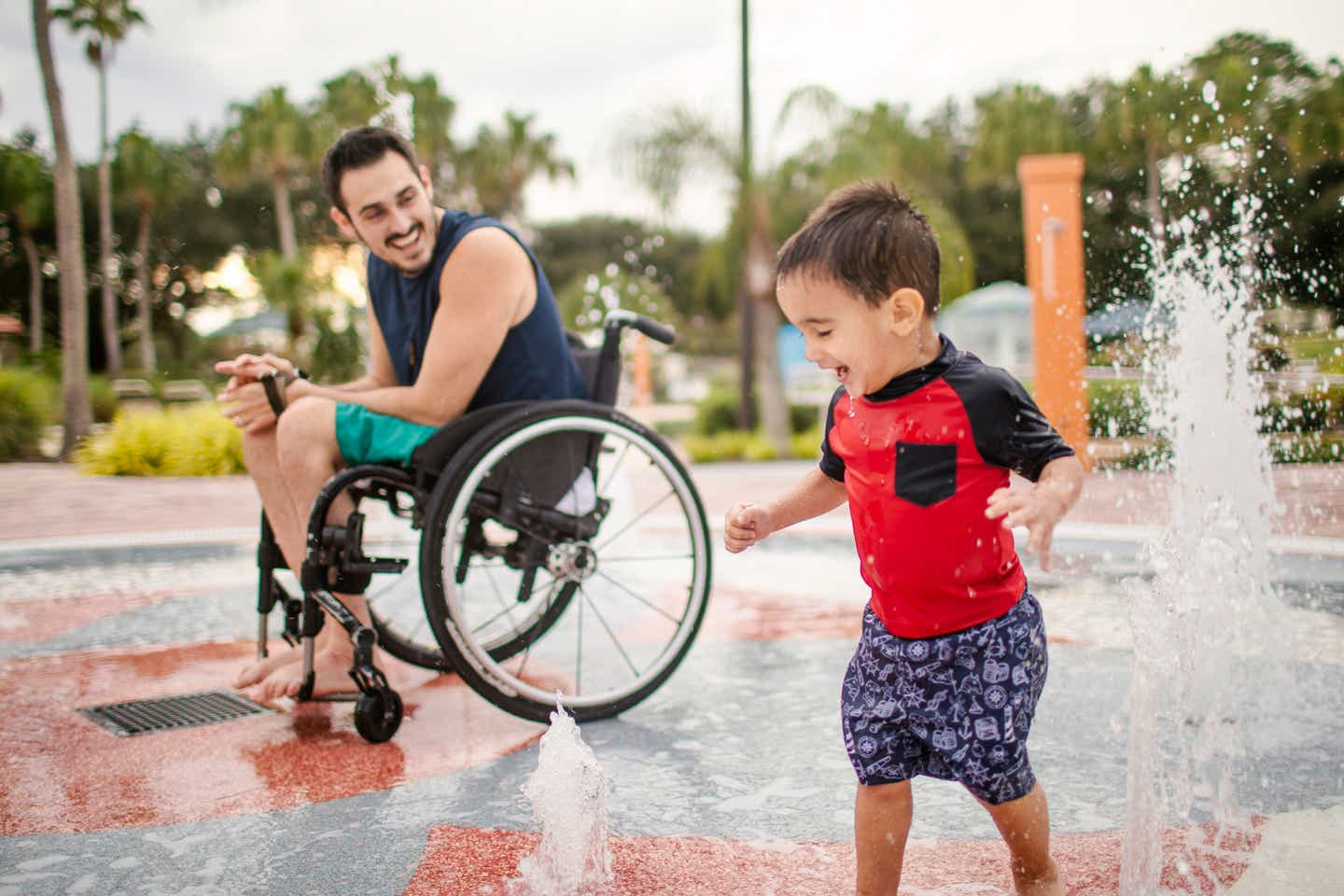 Author, Danny Pitaluga (left), and son, Joey (right), wear their swimsuits near a fountain park area at our Orange Lake Resort located in Orlando, Florida.