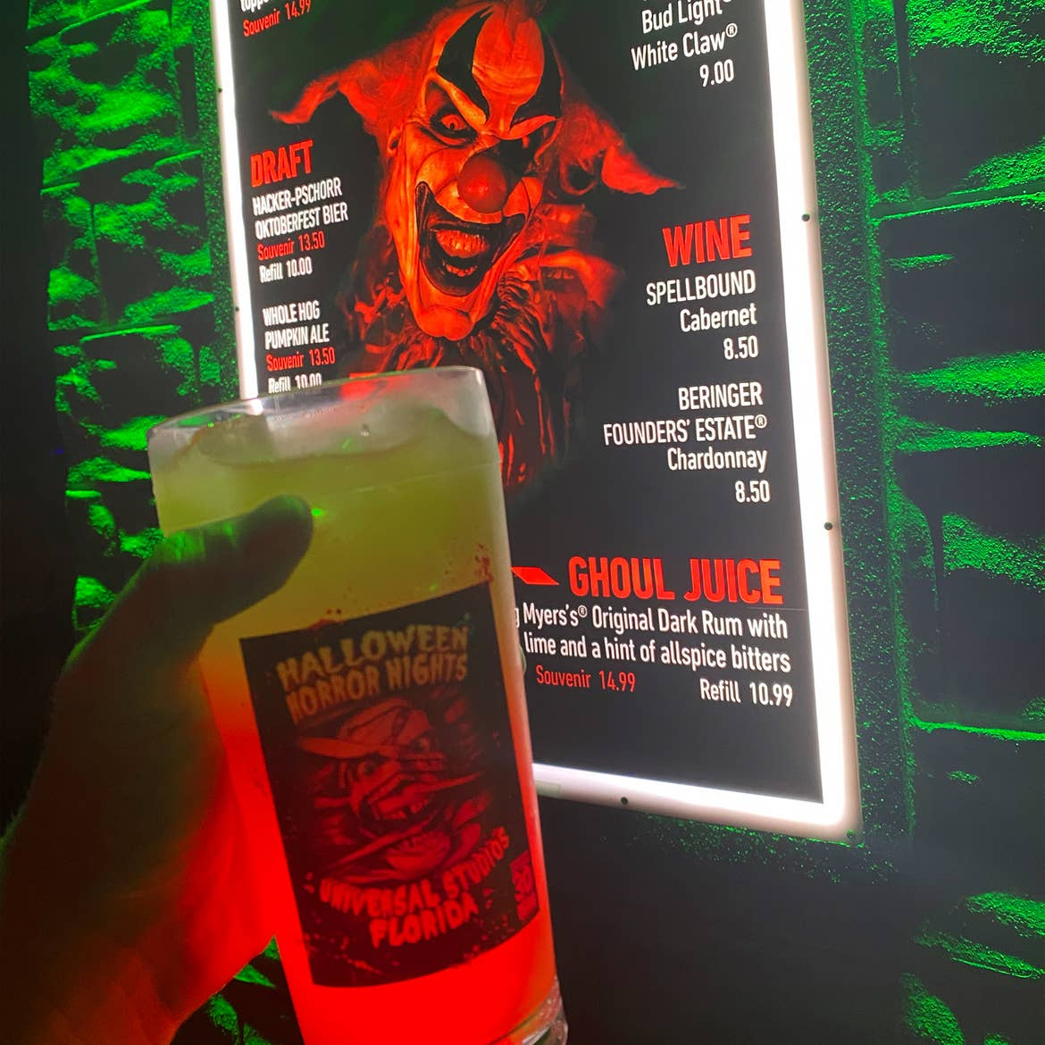 A mixed cocktail drink in a Halloween-themed glass.