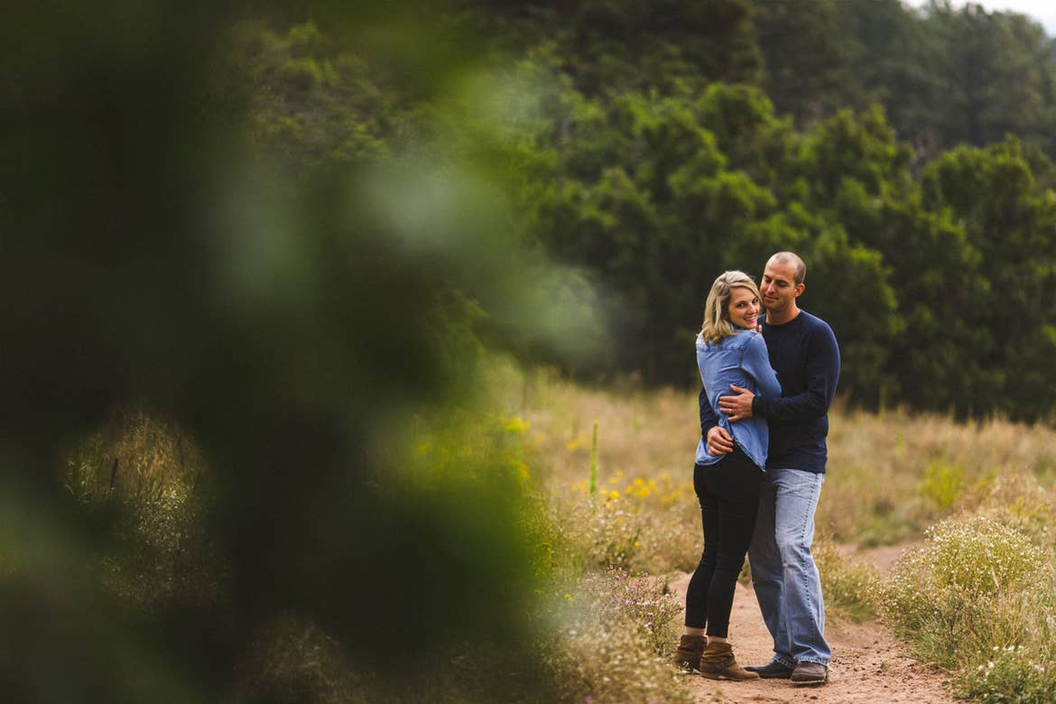 A couple stands outdoors holding embracing each other surrounded by a lush environment.