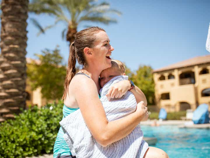 Adult holding young child wrapped in a towel by the pool at Scottsdale Resort in Scottsdale, Arizona.