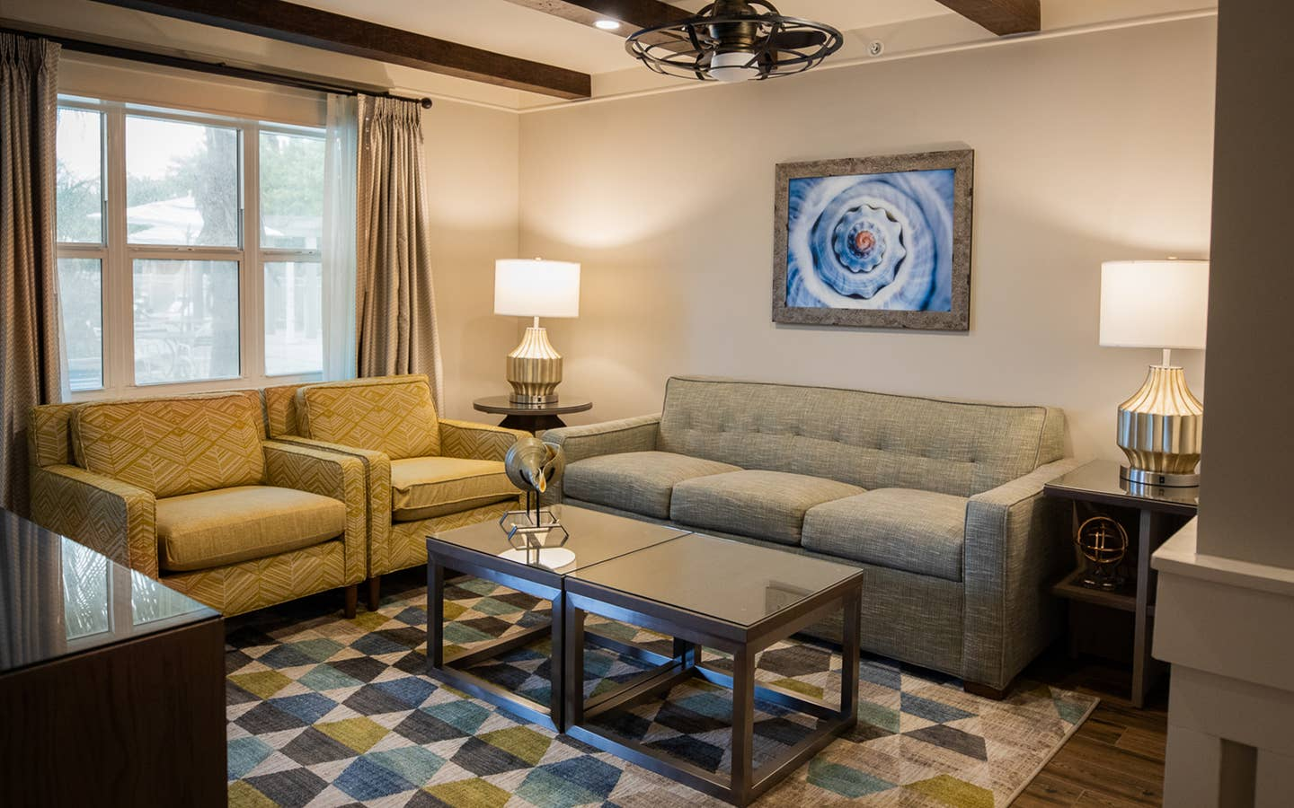 Living room with couch and two chairs in a two-bedroom Signature Collection villa at Cape Canaveral Beach Resort.
