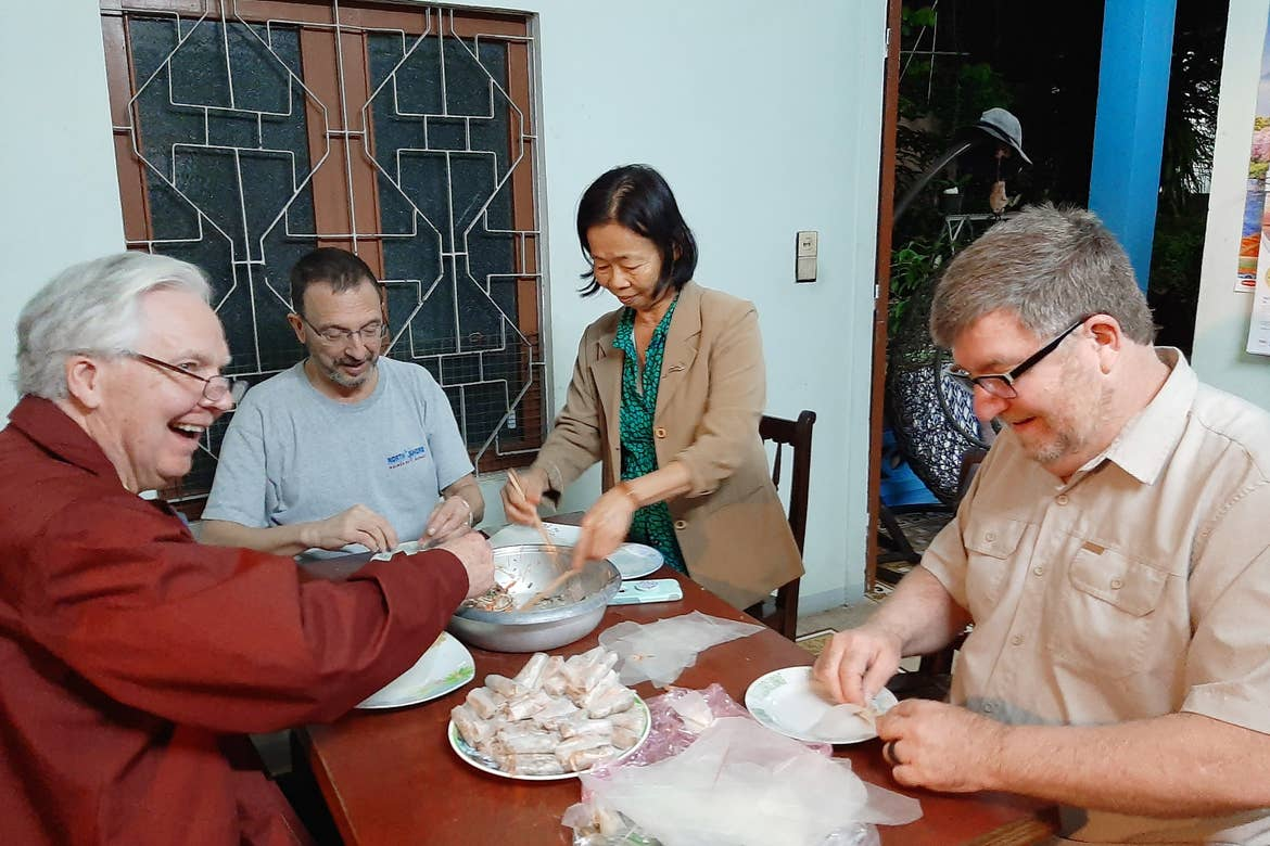Three caucasian men (front-left, front-right, and back-left) sit at a table as a Vietnamese woman serves a traditional dish.