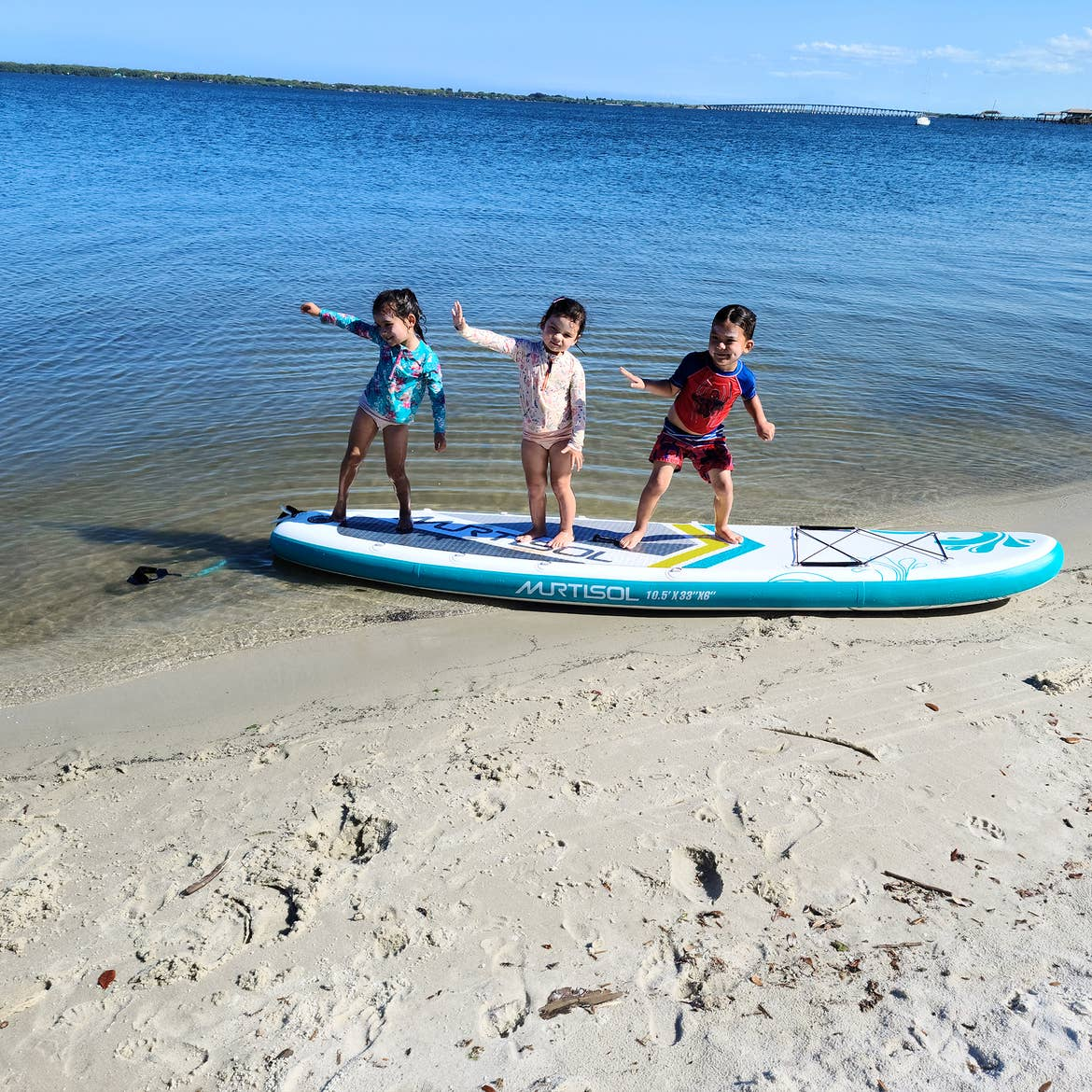Three Asian Pacific Islander toddlers (left to right: Two girls and a boy) wear pink and blue swimsuits while standing on a paddle board on the sands and water of a beach.