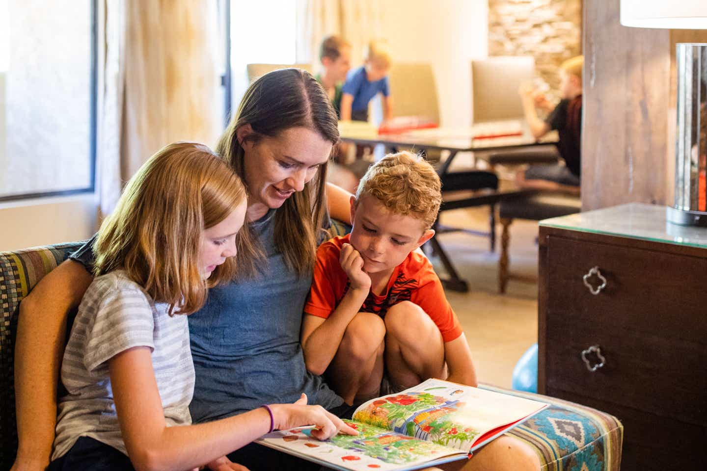 Author Jessica Averett (middle) sits in their villa reading to her daughter (left) and son (right) at our Scottsdale Resort.