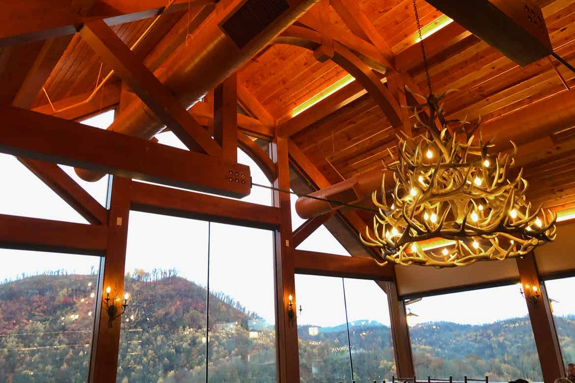 The interior of Anakeesta's Cliff Top restaurant with a view of the mountain range, antler chandelier, and log architecture.