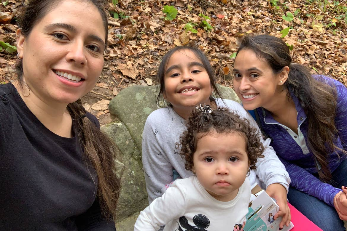 Featured author, Andrea Beltran (right), poses with her sister (left) and two nieces (middle) surrounded by dropped fall foliage.