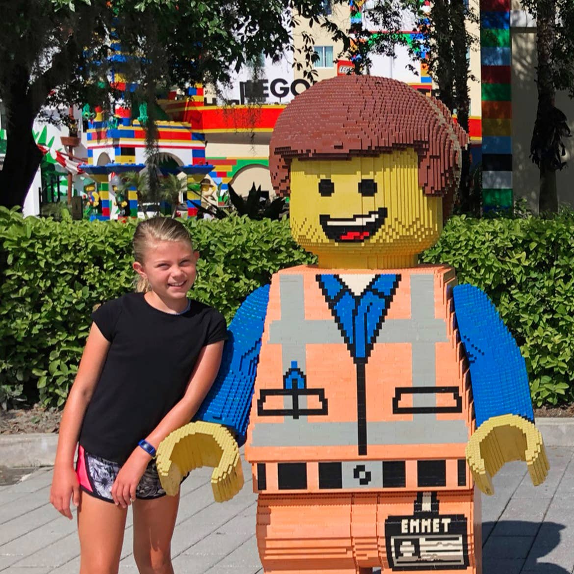 A young girl in a black t-shirt (left) stands next to an oversized LEGO figure.