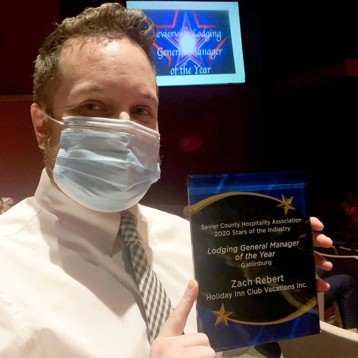 HICV general Manager, Zach Rebert, wears a mask while holding his 'Lodging General Manager of the Year' award.