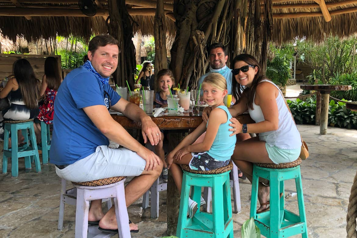 Featured Contributor, Chris Johnston (far-right), sits with her husband, Josh (back-right), and two daughters, Kyler (middle-left) and Kyndall (front-right), and family friend, Anthony (left), at a tiki-inspired dining table.