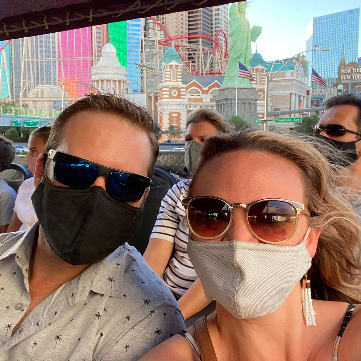 A caucasian woman wearing sunglasses and a face mask (right) poses near a caucasian man wearing sunglasses and a face mask (left) while seated on a double decker bus tour near the Las Vegas Strip.