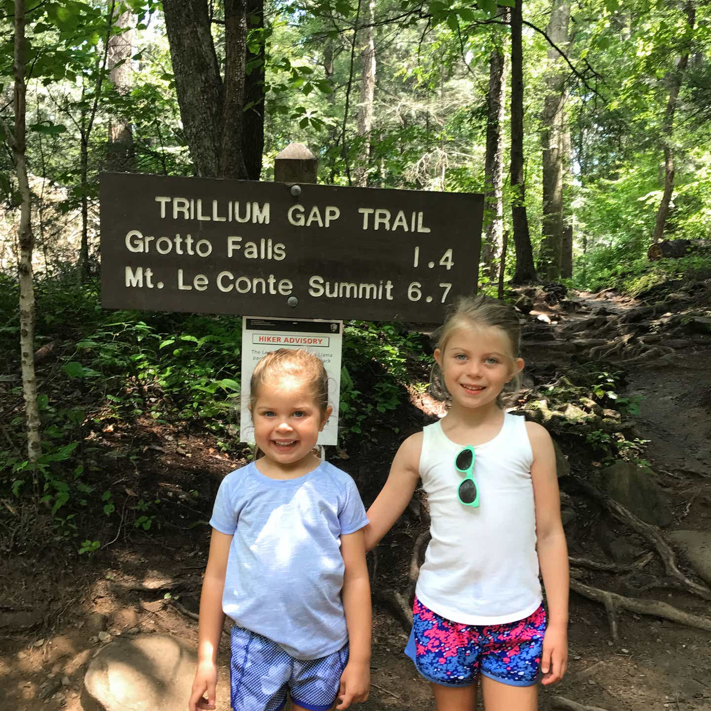 Author, Chris Johnstons' daughters, Kyndall (right), and Kyler (left) pose with a brown, wooden sign that reads, 'Trillium Gap Trail, Grotto Falls 1.4, Mt. LeConte, Summit 6.7.'