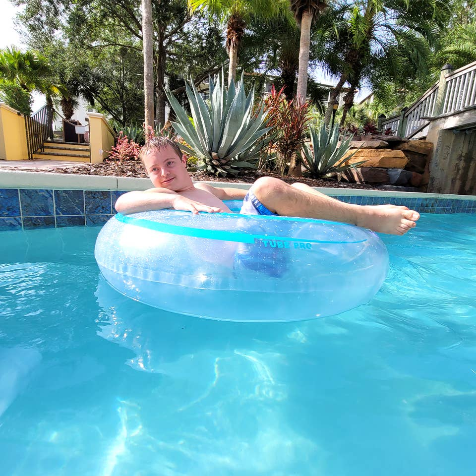 A young boy sits in an inner tube while floating down a lazy river.