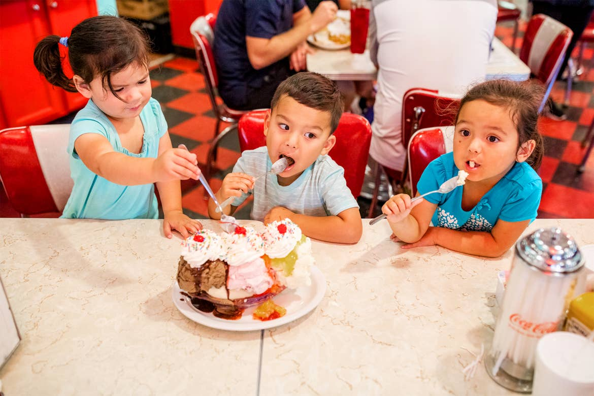 Three Asian Pacific Islander children sit at a table enjoying a large ice cream sundae in a diner.