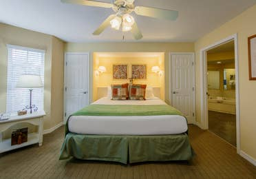 Bedroom with ceiling fan and attached bathroom in a one-bedroom Presidential villa at Hill Country Resort in Canyon Lake, Texas