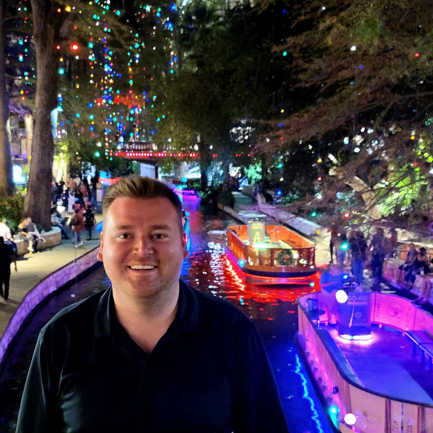 Author, Chris Harms, stands with in front of the San Antonio Riverwalk decorated for the holidays.