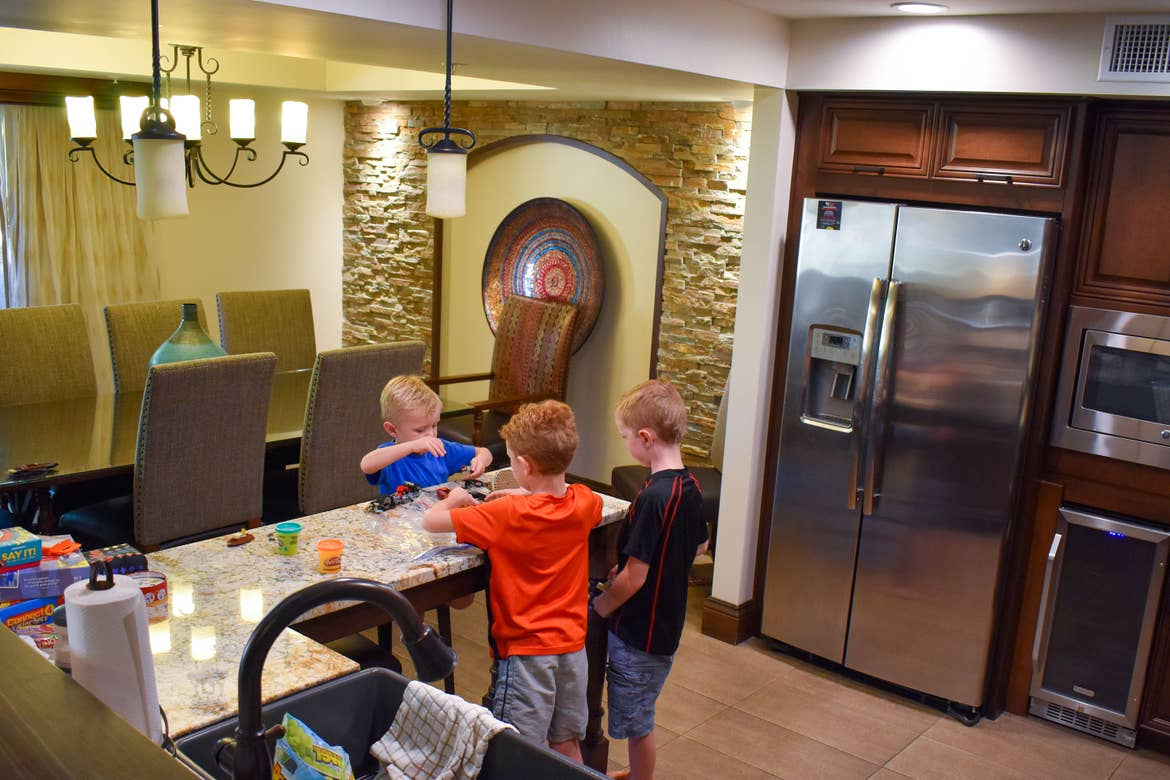 The Averett boys play with toys on the kitchen countertop of our Scottsdale resort villa with a large dining room table and seating for several people in the background.