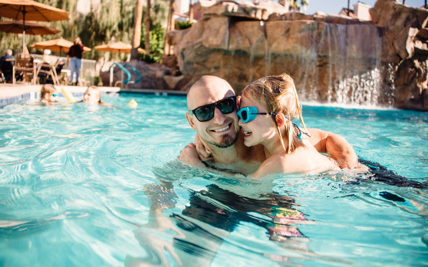 Father and daughter in Watering Hole outdoor pool at Desert Club Resort in Las Vegas, Nevada.