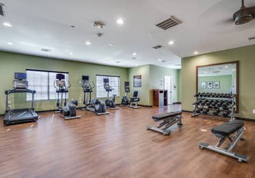 Fitness center with treadmill, elliptical machines, and free weights at Piney Shores Resort in Conroe, Texas