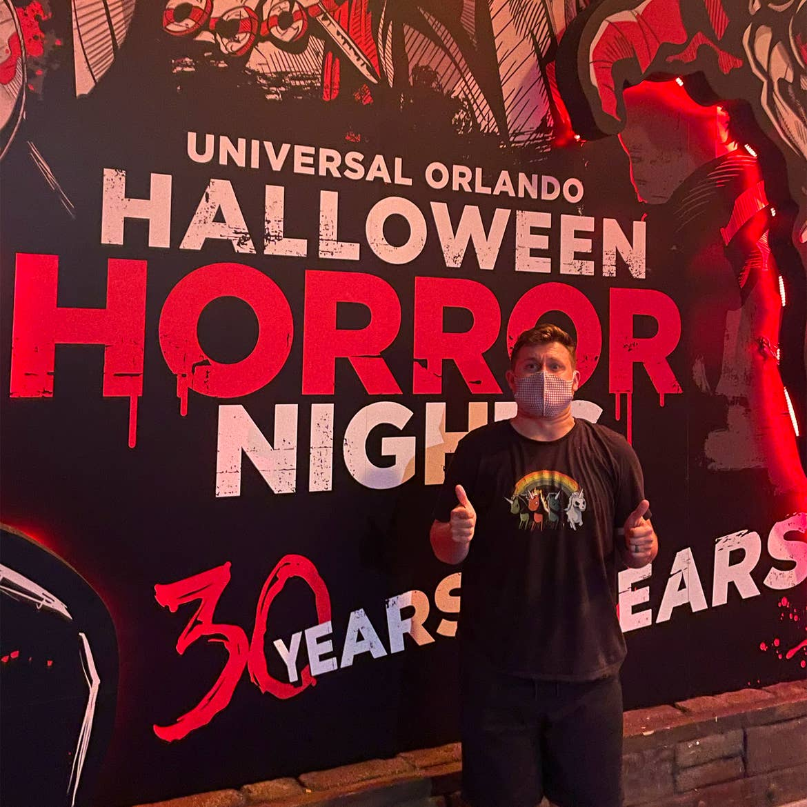 A male wearing black t-shirt and shorts stands in front of a Halloween mural.