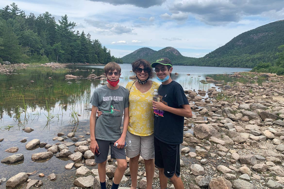 Author, Jennifer Probst (left), and her sons (middle and right) stand off-trail near a river while wearing their masks.