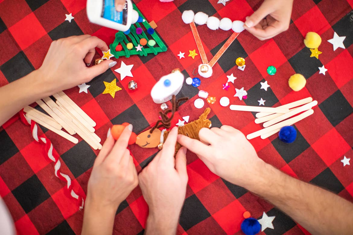 A Jollydays craft activity with various supplies to make Christmas tree ornaments.