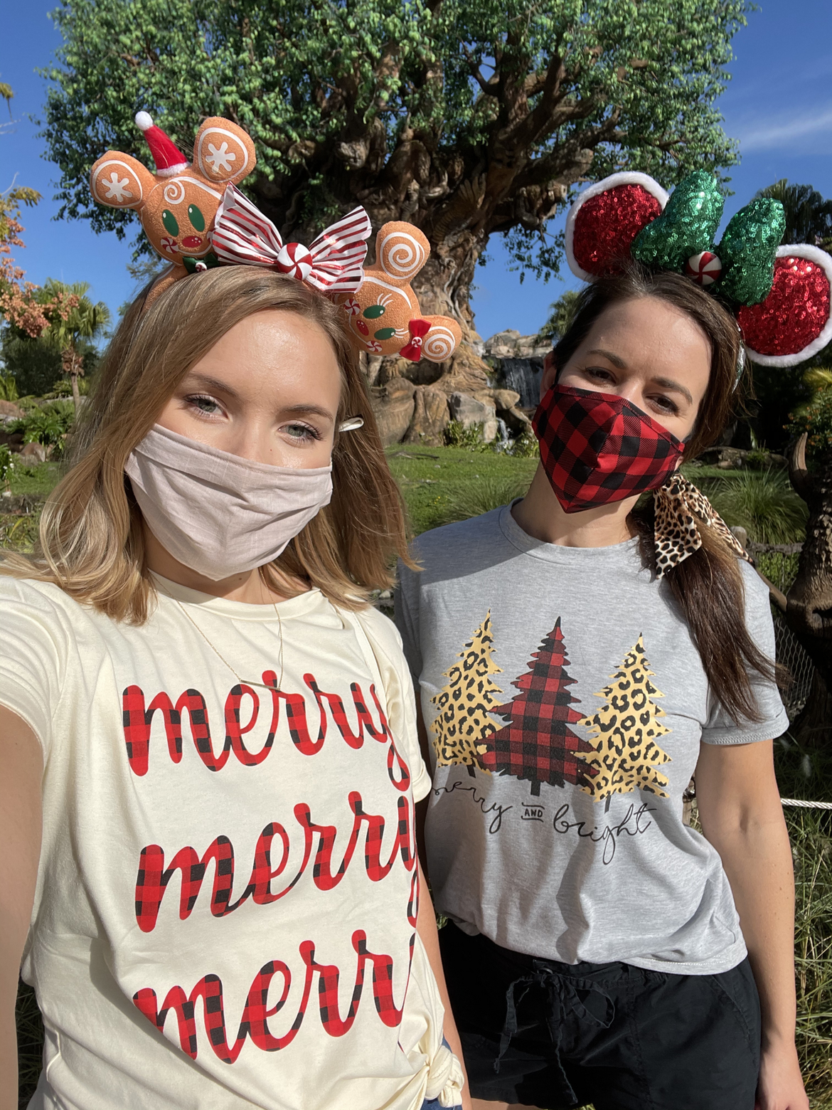 Author, Kelly Nelson (left), and Jenn C. Harmon (right) wear holiday inspired shirts and Minnie Mouse Ears within front of the Christmas Tree at Disney's Animal Kingdom Theme Park at Walt Disney World® Resort.