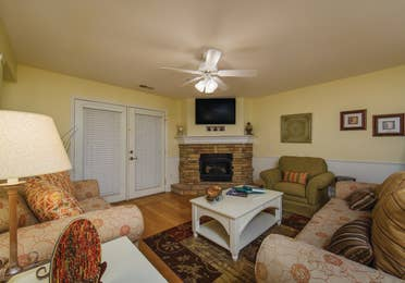 Living room with fireplace and TV in a two-bedroom presidential villa at the Holiday Hills Resort in Branson Missouri.