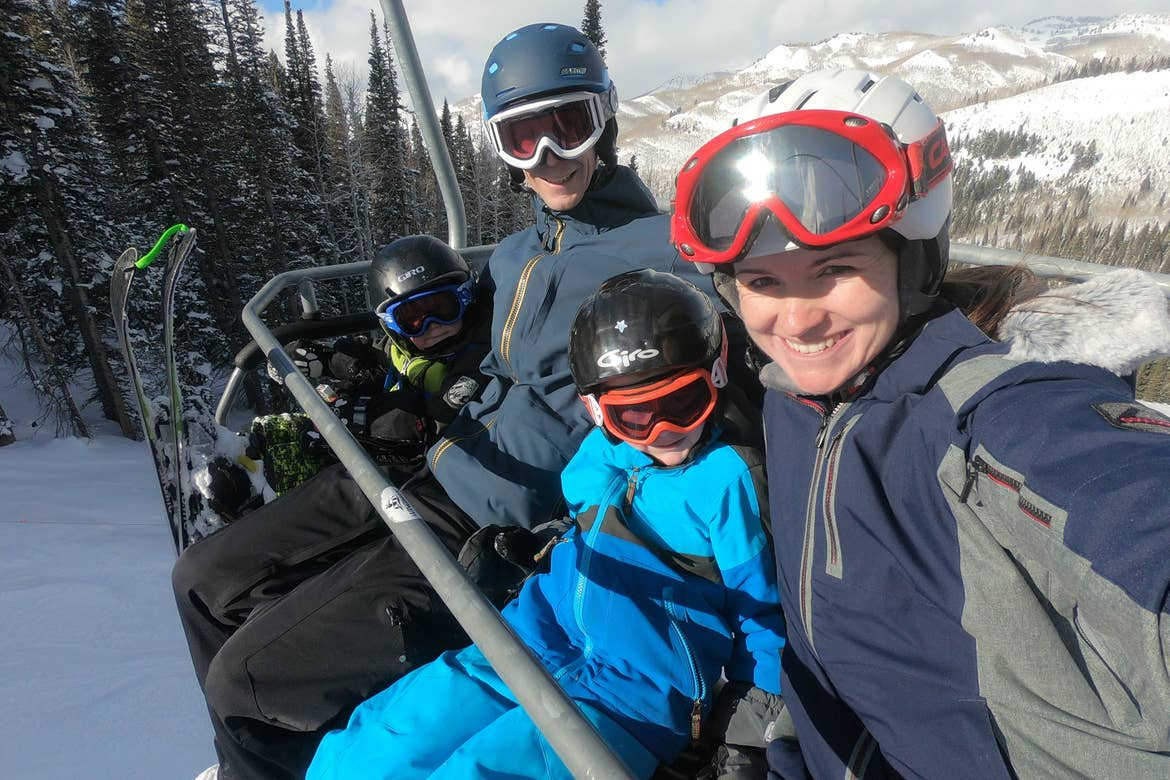 Author, Jessica Averett, and her family sit on the ski lift in winter apparel and ski gear.