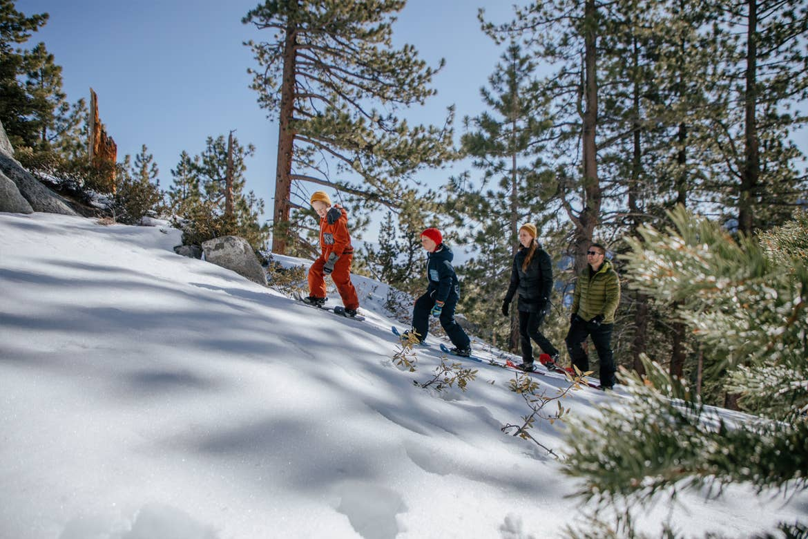 A family goes snowshoeing up a snowy incline near Lake Tahoe.