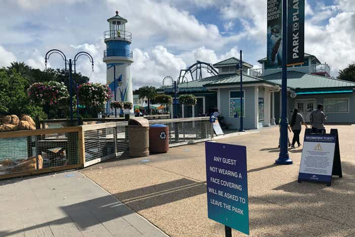 SeaWorld Orlando lighthouse and boardwalk entrance clad with safety signage to enforce social distancing.