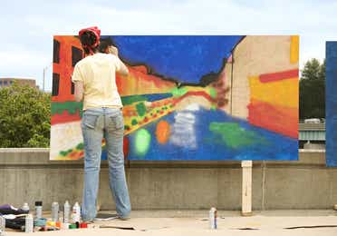 Woman painting on a large canvas outdoors