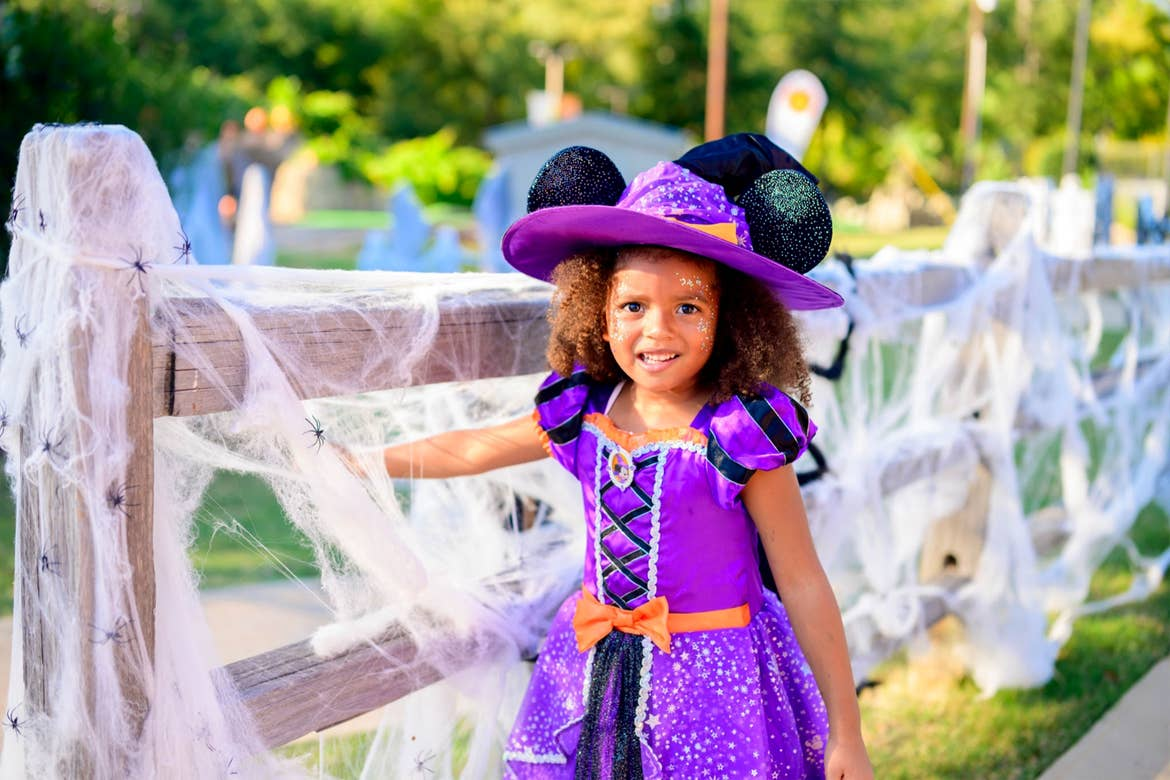 A young girl stands next to a spider-web fence wearing a purple witch costume.