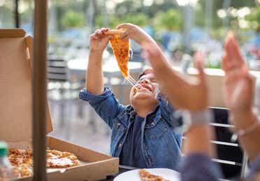 Young boy eating pizza at Orange Lake Resort near Orlando, Florida